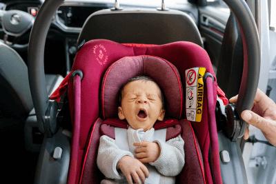 rote Babyschale mit müdem Baby